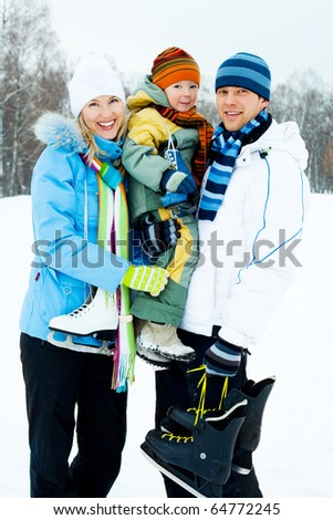 happy young parents going ice skating with their son