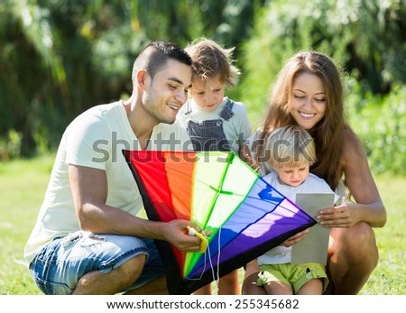 Happy young parents helping kids with toy kite at summer day. Focus on man  - stock photo