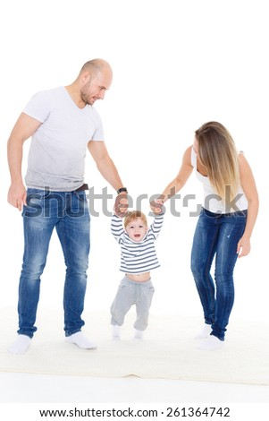 Happy young parents helping their little son doing the first steps. - stock photo