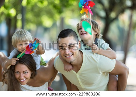 Happy young parents holding kids with toy windmills at summer day  - stock photo