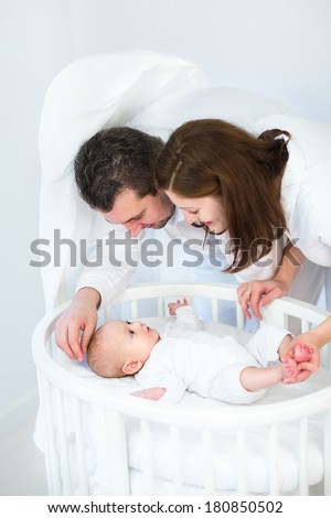 Happy young parents looking at their cute smiling baby son in a white round crib