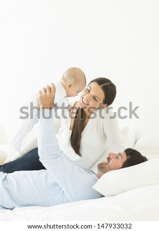 Happy young parents playing with little baby in bed - stock photo