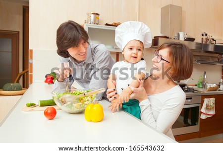 happy young parents with a baby preparing salad on the kitchen