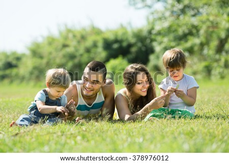 Happy young parents with two kids lying on grass in sunny summer park