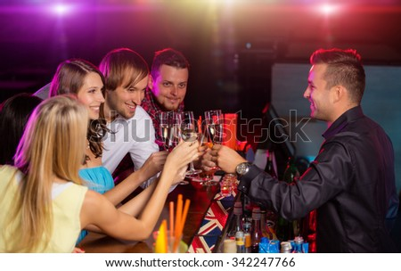 Happy young people clinking with champagne glasses in nightclub.