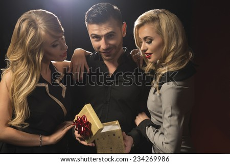 Happy young people give each other gifts near the Christmas tree.  - stock photo
