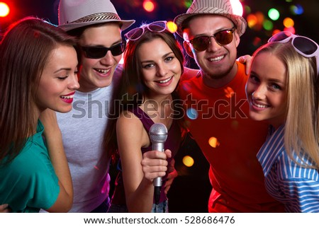Happy young people having fun singing at a party
