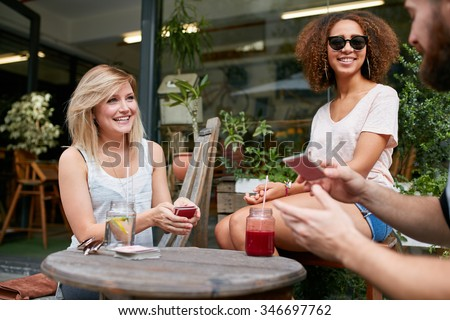 Happy young people playing cards at outdoor coffee shop. Three friends playing poker card game at sidewalk cafe. - stock photo