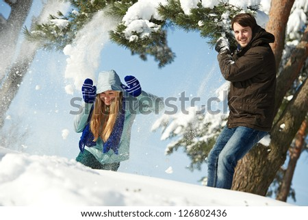 happy young people playing with snow splashes in sunny winter outdoors - stock photo