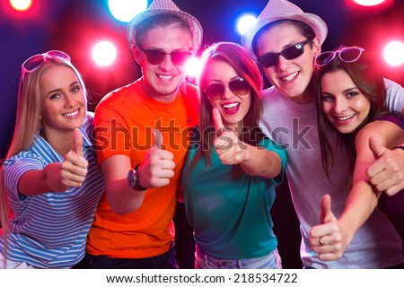 Happy young people show thumb up