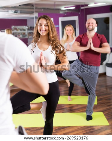 Happy young people studying new position at yoga school - stock photo