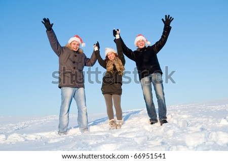 happy young people with hands up and red hats in snowy winter outdoors - stock photo