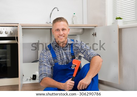 Happy Young Plumber With Adjustable Wrench Sitting In Kitchen Room - stock photo
