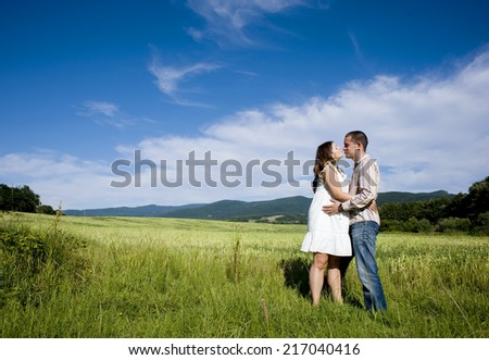 Happy young pregnant couple hugging and kissing in nature
