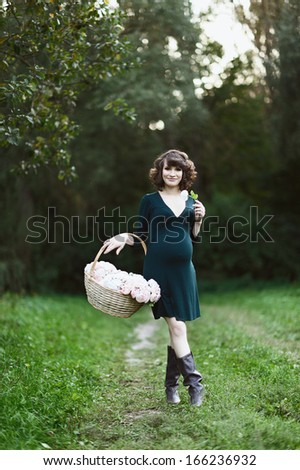 Happy young pregnant woman in the park - stock photo