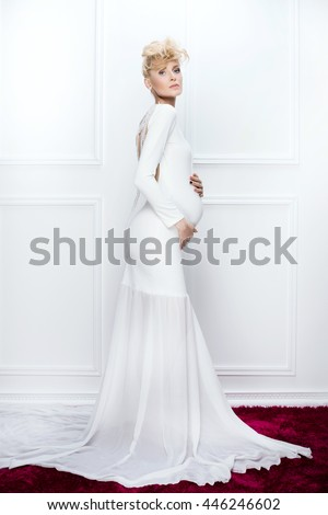 Happy young pregnant woman posing in white elegant dress. Studio shot. Conceptual photo.