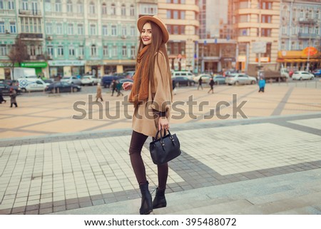 Happy young pretty woman with hat walking down the street. Vacation Europe