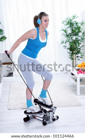 Happy young pretty women exercising on stepper at home - stock photo