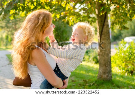 Happy young red-haired mother holding a blond child for a walk in the park in summer - stock photo
