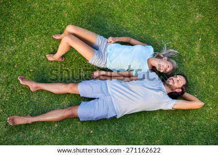 Happy young relaxed couple in love laying down on the grass overhead