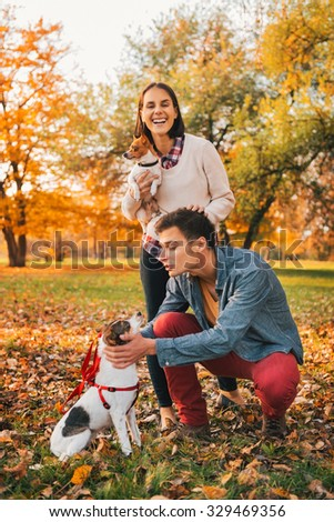 Happy young relaxed couple walking in autumn park and playing with dogs - stock photo