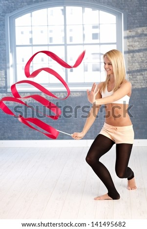 Happy young rhytmic gymnast exercising with ribbon. - stock photo