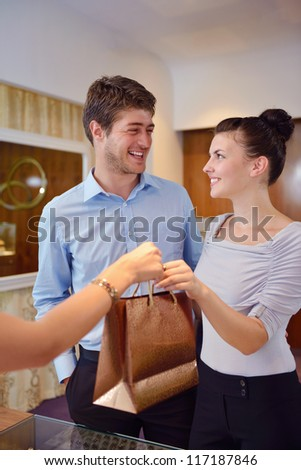 happy young romantic couple in love buy jewelry ring in luxury store - stock photo