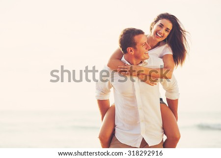 Happy Young Romantic Couple Playing and Having Fun on the Beach - stock photo