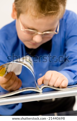 Happy young school boy reading a magazine