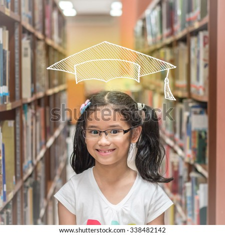 Happy young school student girl kid with imaginary doodle graduation cap standing among bookshelves smiling thinking library book learning resource is awesome for future educational/ academic success  - stock photo
