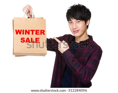 Happy young shopper with finger point to paper bag for showing phrase of winter sale