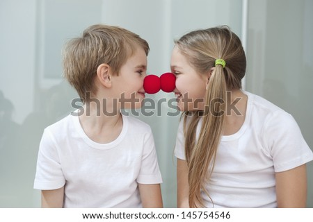 Happy young siblings in white tshirts rubbing clown noses against each other - stock photo
