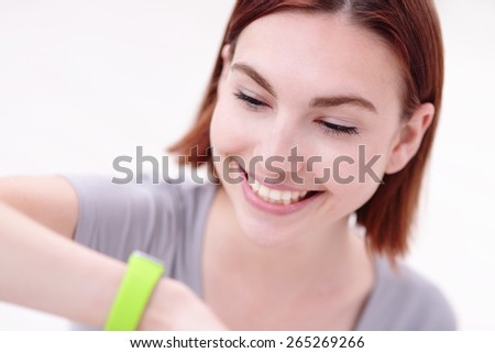 Happy young smile woman look smart watch and relax sit on the floor, caucasian beauty - stock photo
