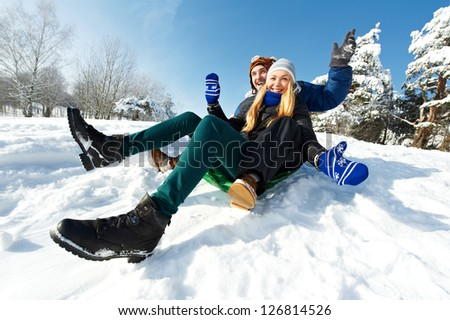 happy young smiling adult people in warm clothing sledding on snow at winter outdoors - stock photo