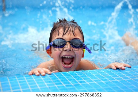 Happy young smiling boy in the swimming pool - stock photo