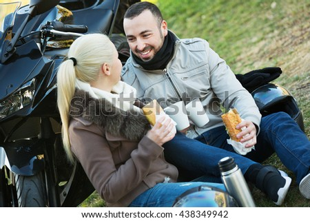 Happy young smiling couple having picnic with coffee near cycle - stock photo