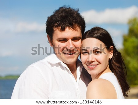 Happy young smiling couple in summer day on the river coast