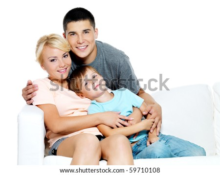 Happy young smiling family with kid sitting on white sofa - Isolated - stock photo