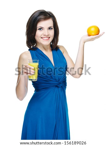 Happy young smiling girl in a blue dress. Holding a glass of orange juice. Isolated on white background