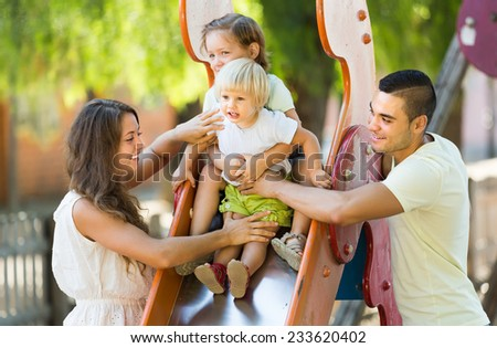 Happy young smiling parents with two kids playing at children's slide. Focus on girl  - stock photo