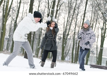 happy young smiling people playing snowball in warm clothing at winter outdoors - stock photo