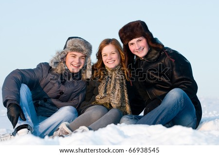 happy young smiling people sitting in snow at winter outdoors - stock photo
