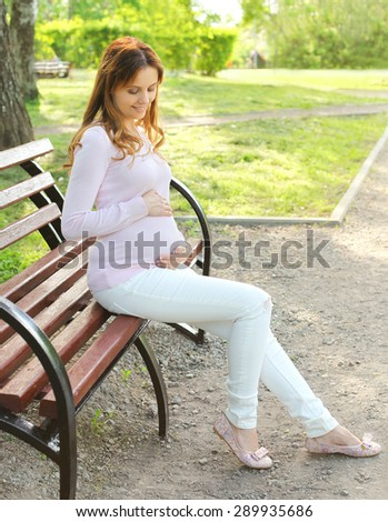 Happy young smiling pregnant woman resting on the bench in city park - stock photo