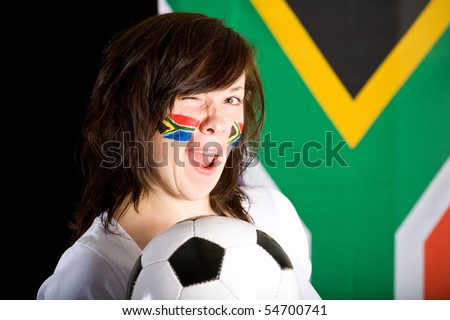 happy young soccer supporter, flags on her cheeks, holds football ball, south africa flag as background