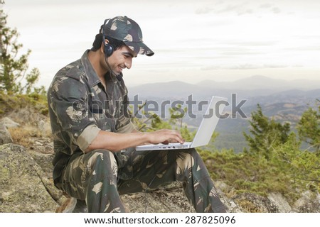 Happy young soldier using laptop , outdoors - stock photo