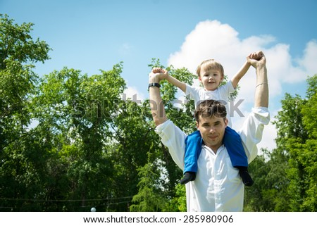 Happy young son on his shoulders at the father against the backdrop of the sky and green forest in summer warm day in the summer - stock photo