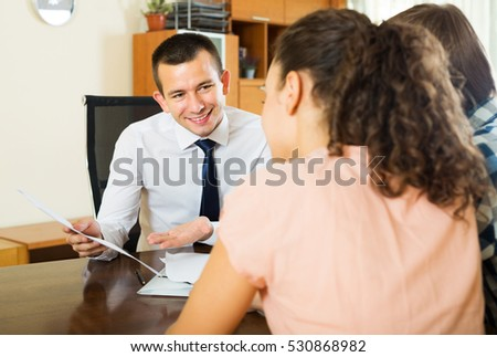 Happy young spouses and positive salesman with documents at agency