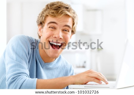 Happy young student is excited while browsing the internet with