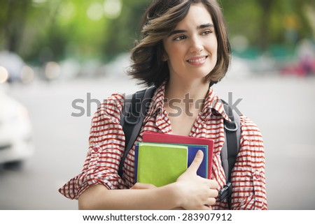 Happy young student outdoors - stock photo