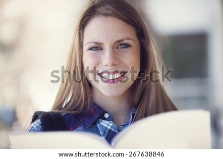 Happy young student reading a textbook - stock photo